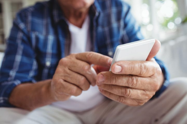 senior man using mobile phone at home