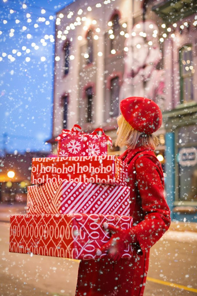 women in red coat with gifts boxes