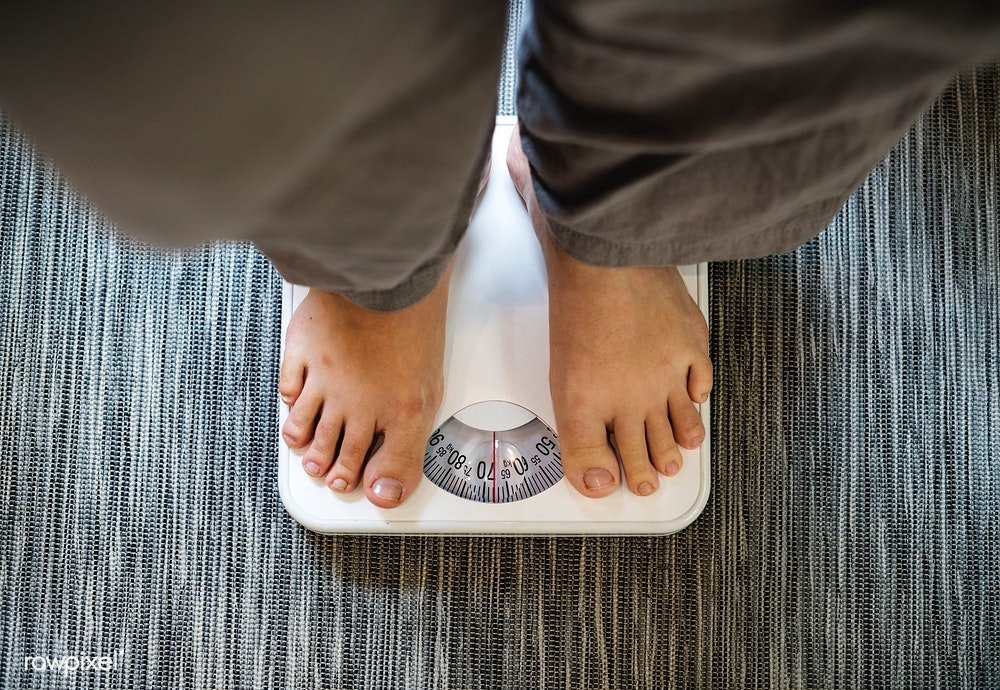 Woman standing on scale 1 - 7 Easy Tips to Lose Weight When You are Over 200 Pounds