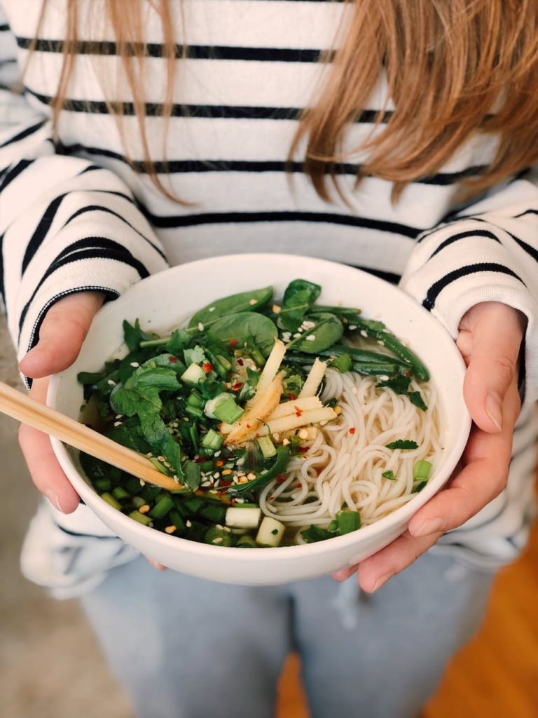 woman holding a bowl of Healthy Noodle Meal