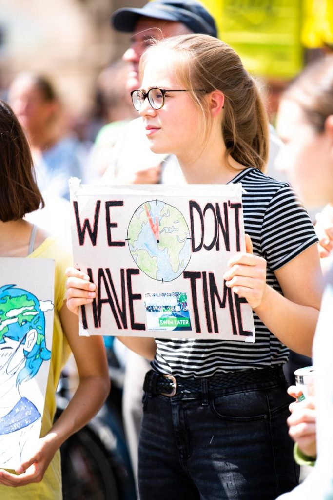 a girl holding a We Don't Have Time sign
